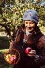 Mujer sosteniendo recogedor de fruta - foto de stock