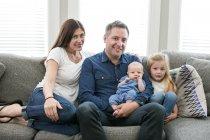 Portrait of family sitting on sofa — Stock Photo