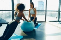 Two young women exercising in gym — Stock Photo