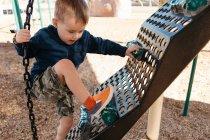 Garçon grimpant sur le cadre d'escalade de terrain de jeu — Photo de stock