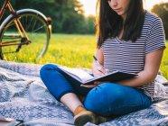 Donna che scrive in libro su coperta — Foto stock
