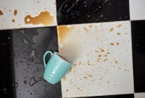 Cup on floor surrounded by spilt coffee — Stock Photo