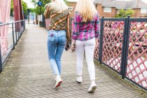 Girls walking across bridge and holding smartphones — Stock Photo