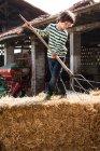 Boy on straw bale with pitchfork — Stock Photo