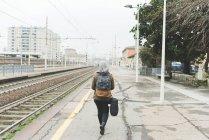 Женщины рюкзаком на железнодорожной платформе — стоковое фото
