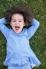 Молодая девушка лежит на траве — стоковое фото