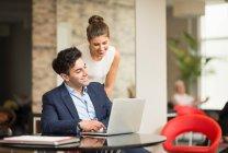 Empresario y mujer mirando portátil - foto de stock