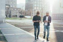 Hipsters marcher dans la ville tout en regardant les smartphones — Photo de stock