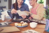 Frau am Tisch mit Großmutter — Stockfoto