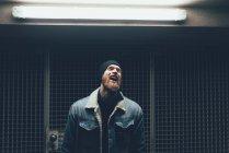 Хипстер смеется в дверях темного города — стоковое фото