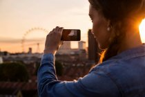 Young woman photographing skyline — Stock Photo