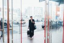 Бізнес-леді потягнувши візки багажу — стокове фото