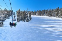 Skiers on ski lift moving up snow covered landscape — Stock Photo