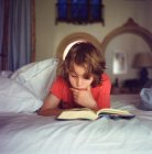 Boy relaxing on bed, reading book — Stock Photo