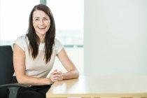 Portrait de femme d'affaires assise au bureau — Photo de stock