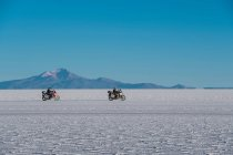 Men riding motorcycles on salt flats — Stock Photo