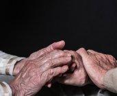 Las manos de la mujer mayor y el hombre - foto de stock
