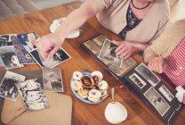 Senior women looking at old photographs — Stock Photo