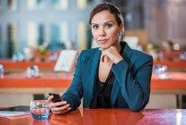 Femme d'affaires à l'aide de téléphone portable au café — Photo de stock