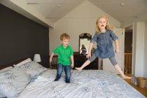 Mädchen und Bruder springen auf Bett — Stockfoto