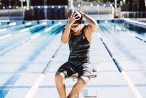 Пловец сидит в конце бассейна — стоковое фото