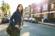 Jovem mulher de pé na estrada — Fotografia de Stock