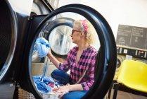 Femme insertion linge dans la machine à laver — Photo de stock