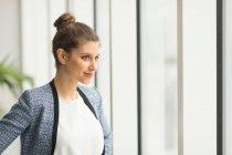 Onfident empresaria mirando a través de la ventana - foto de stock