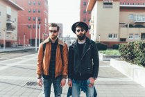 Amigos hipster de pie en urbanización de la ciudad - foto de stock