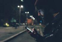 Hipster sulla strada della città guardando smartphone — Foto stock