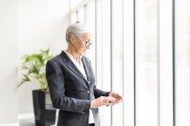 Reife Geschäftsfrau schaut aufs Smartphone — Stockfoto