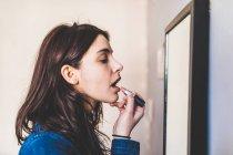 Young woman applying lipstick — Stock Photo