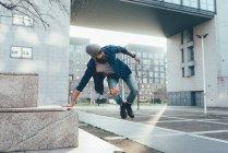 Hipster che salta in aria praticando il parkour — Foto stock