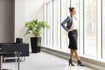 Businesswoman looking through office window — Stock Photo