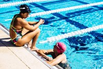 Swimmer sitting at end of pool — Stock Photo