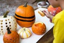 Boy lifting pumpkin — Stock Photo