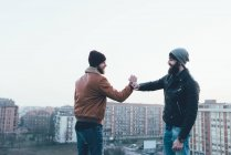 Male hipsters fist bumping above cityscape — Stock Photo
