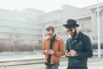 Hipsters regardant les smartphones — Photo de stock