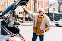Человек держит дверь багажника автомобиля , — стоковое фото