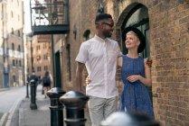 Young couple walking along street — Stock Photo