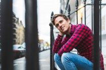 Mann sitzt neben Geländer — Stockfoto