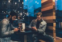 Hipsters au café trottoir en regardant les smartphones — Photo de stock