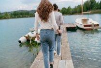 Amigos paseando por el muelle - foto de stock