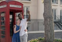Young couple beside red telephone box — Stock Photo