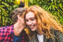 Uomo sussurrando nelle donne orecchio — Foto stock