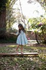 Girl balancing on wooden step — Stock Photo