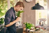 Шеф-повар нюхает свежие травы — стоковое фото