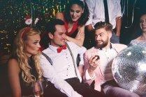 Друзі, які сидять разом на вечірці — стокове фото