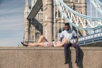 Giovane coppia rilassante sul muro — Foto stock