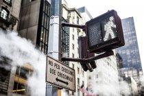 Пешеходный знак и небоскребы — стоковое фото